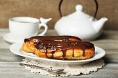 image of eclairs  - Tasty eclairs and cup of tea on wooden table - JPG