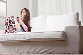 foto of long tongue  - rascal girl showing her tongue stuck out as a joke while using her mobile phone in her living room on a couch - JPG