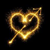 foto of spears  - Speared sparking heart over black background - JPG