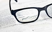picture of graph paper  - financial chart and graph currencies see through glasses lens on financial newspaper business concept - JPG