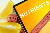 picture of nutrients  - Tablet with words nutrients and measuring tape on white background - JPG