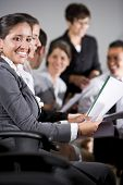stock photo of student teacher  - Young business people or college students sitting in row reading report in presentation - JPG