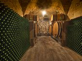 image of wine cellar  - wine bottles and barrels in winery cellar of Tuscany - JPG