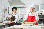 stock photo of chef cap  - Portrait of happy female chefs preparing pasta in commercial kitchen - JPG
