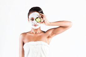 image of mud pack  - Young African woman in Studio doing body care with refreshing cucumber facial mask for young and beautiful skin and relaxation - JPG