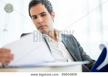 Successful young executive in a jacket sitting reading a report or document