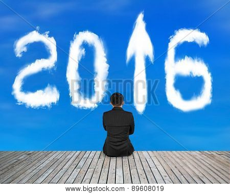 Businessman Sitting On Wooden Floor With 2016 Arrow Sign Clouds