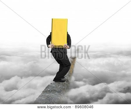 Businessman Carrying Gold Bullion Balancing On Concrete Ridge With Cloudy