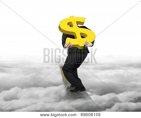 Businessman Carrying Gold Dollar Sign Balancing On Ridge With Cloudy