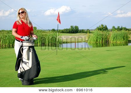 girl with golf bag on golf course