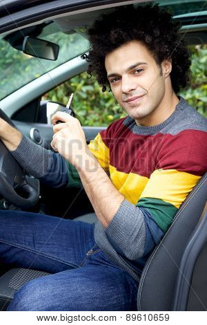 Handsome Man In Car Holding Key Looking Camera