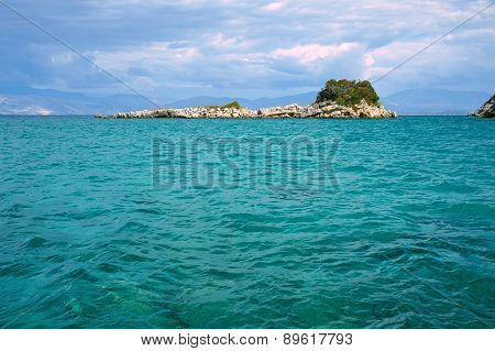 Rocky island in the Ionian sea and the mountains