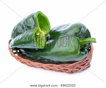 poblano peppers in bamboo basket isolated on white background