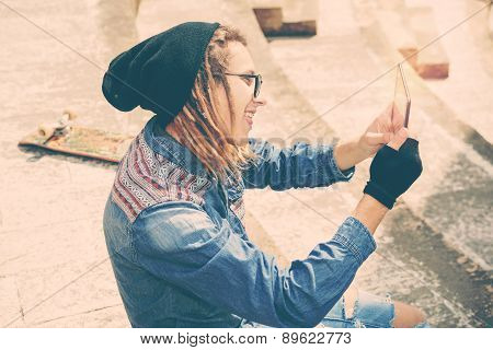 Rasta Guy Taking Selfie Sitting On A Staircase With Tablet Warm Filter Applied