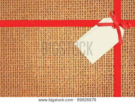 Linen Texture Background With Red Ribbon And Tag