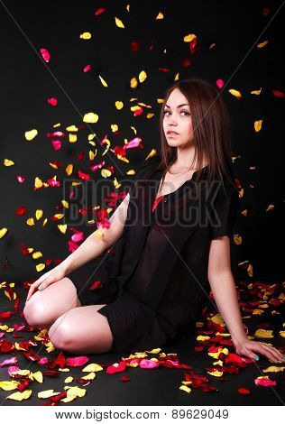 Beautiful Young Woman Sitting Under The Falling Petals