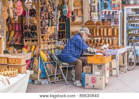 AS-SAWIRA, MOROCCO, APRIL 7, 2015: Seller of leather shoes and other souvenirs sits in front of his stand