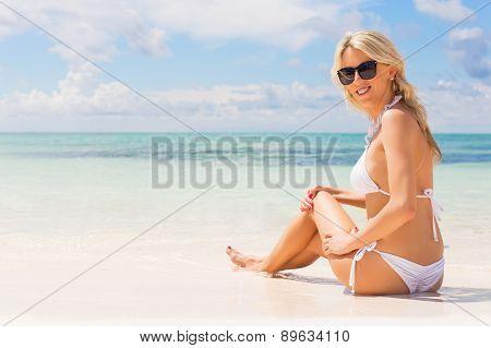 Woman in white bikini enjoying summer day at the beach