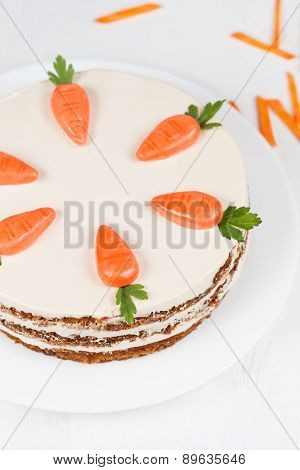 Plate with carrot sponge cake and little orange carrots on cream