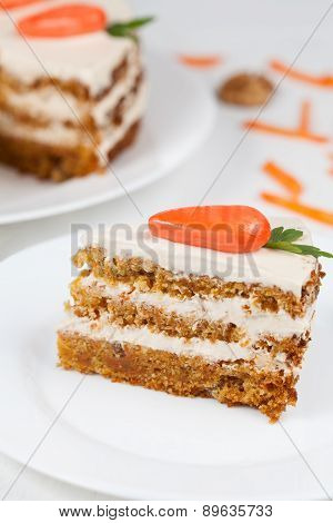 Sliced carrot cake with cream on white plate