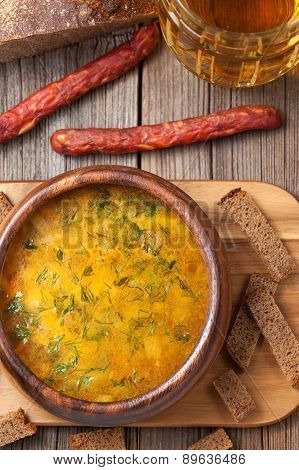 Bowl of rustic traditional chicken broth noodle soup with sausag