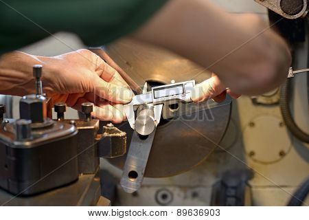 Male Engineer Measuring A Metallic Piece