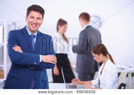 Successful business man standing with his staff in  office