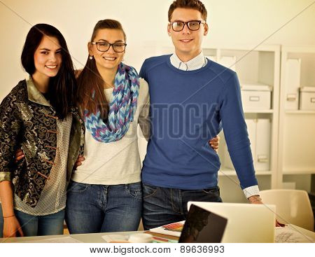 Young business people standing at office near desk.