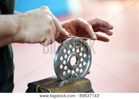Hands Smoothing With A File The Edge Of A Wheel