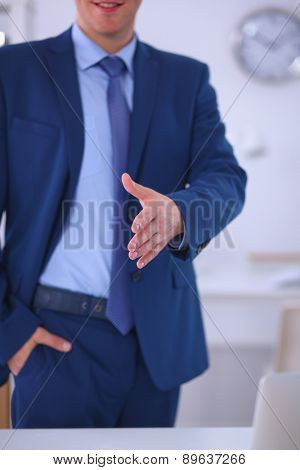 Business and office concept -  businessman with open hand ready for handshake
