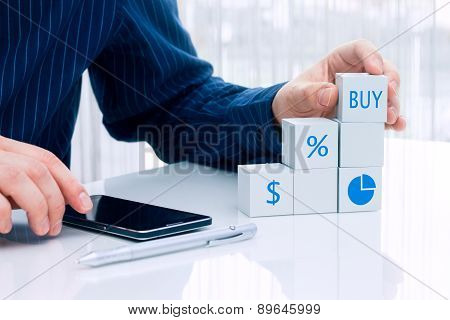 Businessman arranging small blocks with financial symbols