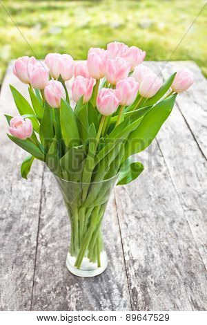 Bouquet Of Light Pink Tulips On The Oak Brown Table In A Clear Glass Vase