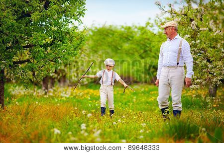 Grandpa With Grandson Walking Through The Spring Garden