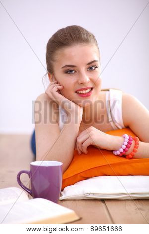 Smiling young woman lying on a white floor with pillow.