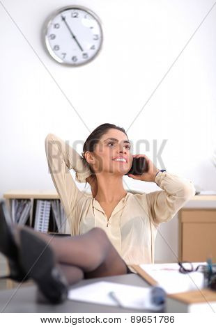 Young businesswoman sitting and talking on phone.