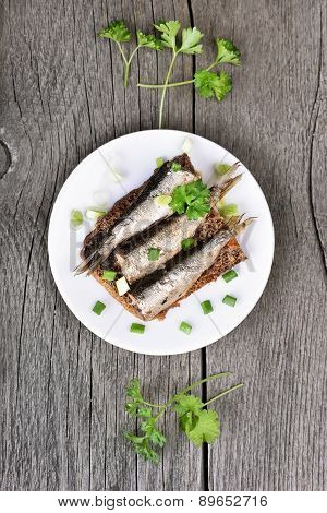 Sprats Sandwich With Herbs On Rustic Table