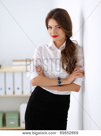 Attractive businesswoman standing near wall in office.