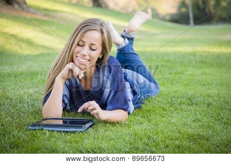 Smiling Young Woman Using Computer Tablet Outdoors at the Park.
