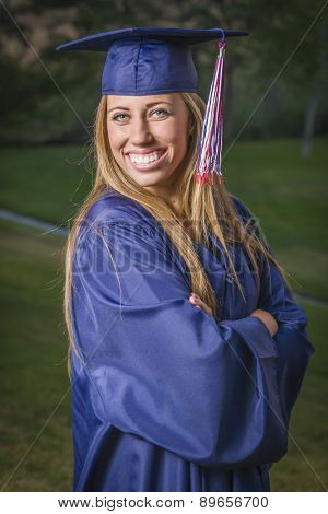Smiling Young Woman Wearing Cap and Gown Outdoors.