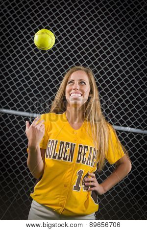 Young Female Softball Player Portrait with Ball in the Air.