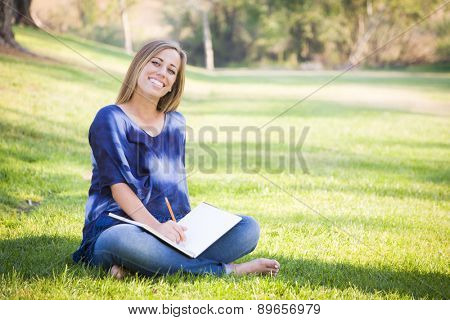 Portrait of a Beautiful Young Woman With Book Outdoors at the Park.