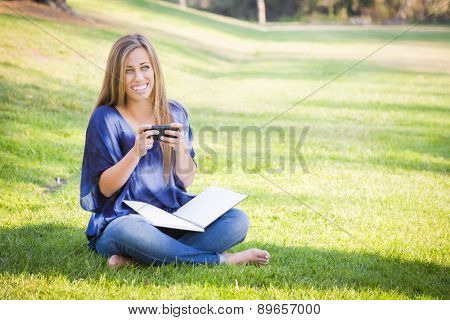 Smiling Young Woman with Book and Cell Phone Outdoors at the Park.