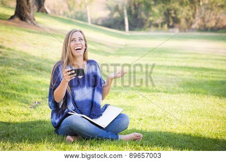 Laughing Young Woman with Book and Cell Phone Outdoors at the Park.