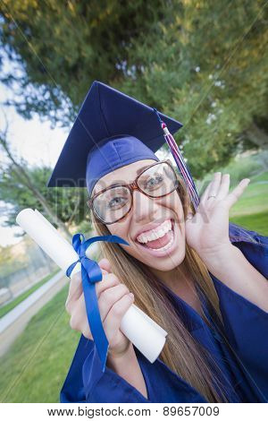 Excited and Expressive Young Woman Holding Diploma in Cap and Gown Outdoors.
