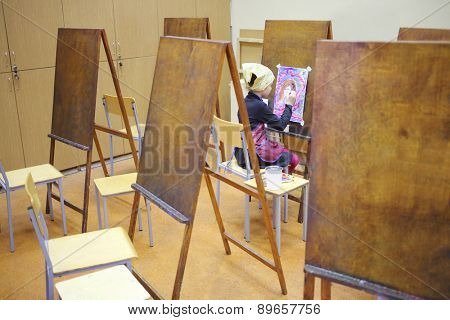 MOSCOW, RUSSIA - MAR 22, 2014: Girl in yellow scarf and apron drawing fantastic picture in art class