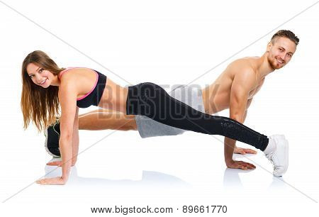 Sport Attractive Couple - Man And Woman Doing Fitness Exercises On The White