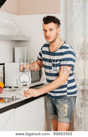 brunette man with stubble in a striped T-shirt the kitchen pouring tea