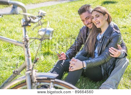 Couple Sitting On The Grass And Relaxing
