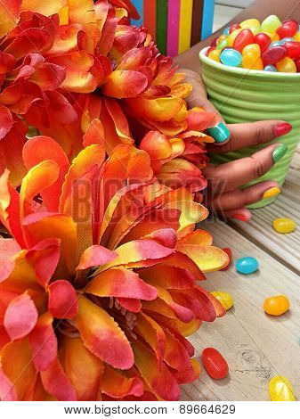 Orange flowers with jelly beans in a teacup
