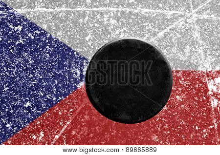 Black hockey puck on ice rink with Czech flag.